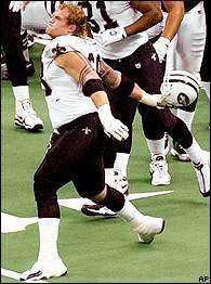 Kyle Turley of the 2001 New Orleans Saints throws a Jet helmet down field.